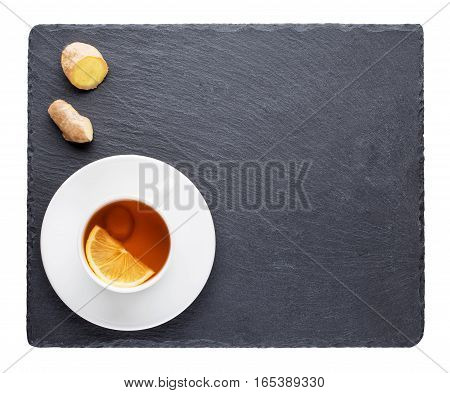 Tea with the lemon and ginger root on slate blackboard isolated on white background