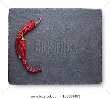 Two dry red pepper on slate blackboard isolated on white background