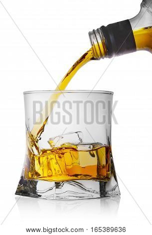 Whiskey pouring from a bottle into a glass with ice isolated on white background