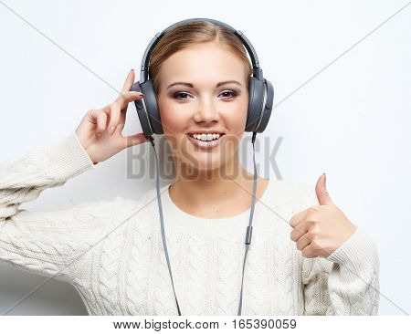 Young beautiful woman listening the music from headphones over white background