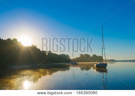 Little sailing boats reflect in the serene water during sunrise.