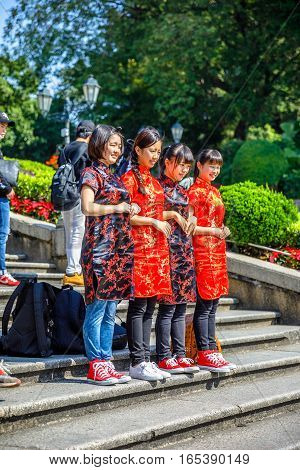 Macau, China - December 8, 2016: Typical Asian teenagers with traditional red kimonos pose for photos on staircase of Ruins of St. Paul's Cathedral, one of most popular tourist attractions of Macau