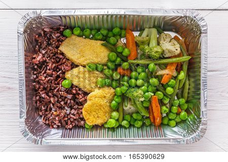 Healthy food restaurant delivery and diet concept. Take away of fitness meal. Weight loss lunch in foil boxes. Meat with brown rice and vegetables on white wood, top view