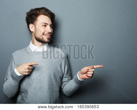a young and handsome businessman pointing up with his finger over grey background
