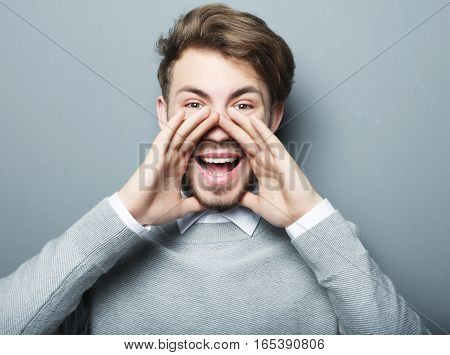 handsome man shouting while looking at camera over grey background