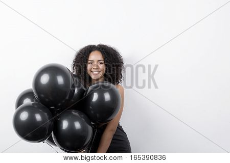 Portrait of a brunette woman having fun with black balloons