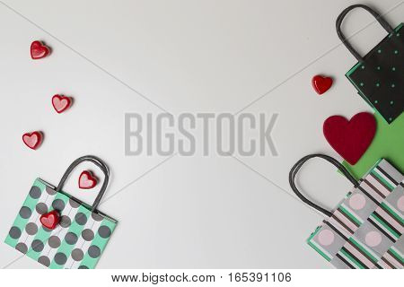 Colourful shopping bags and red hearts on white background. Top view. Flat lay. Copy space for text. Shop, sale, gift, valentines day concept