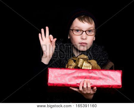 small boy or cute nerd kid in glasses hat and fashionable knitted scarf on black background holds red present box with golden bow and ok gesture