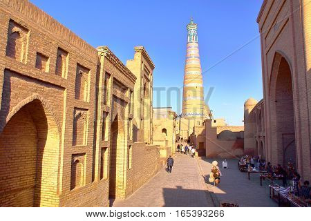 KHIVA, UZBEKISTAN - MAY 6, 2011: An alley inside Khiva old town with The Islam Khodja minaret in the background