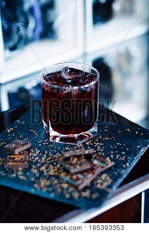 Glass of cherry juice with chocolate pieces over blue background