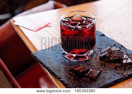 Glass of cherry juice with chocolate pieces over wooden background