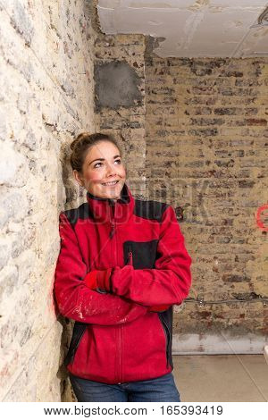 Innovative Craftswoman Leaning Against Brick Wall In Bare Brickwork