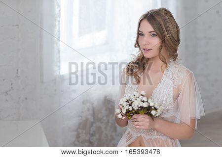 Bride's morning in a bright room. Young sensual woman holds a delicate bouquet of flowers.