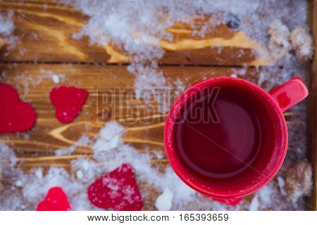 Red cup with tea on a wooden tray in snow. Romantic Valentine's day winter picnic hot tea. Lifestyle time together outdoors Valentine's day. Snowflakes hoarfrost and heart shape on a tray. Copy space
