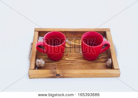 Two red cups with tea on a wooden tray in snow. Romantic winter picnic couple going to drink hot tea. Lifestyle winter walk time outdoors. Snowflakes and hoarfrost on a tray