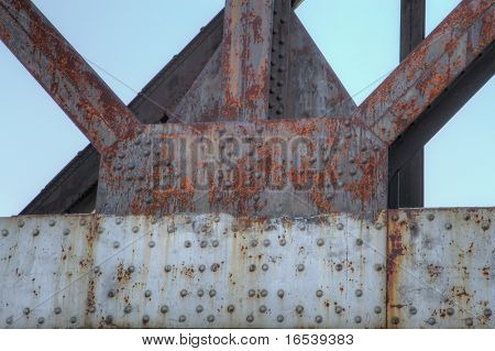 Framework of rusty old steel beams and girders with backdrop sky