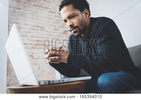 Serious bearded young African man thinking while sitting on sofa at his modern coworking place. Concept of business people using mobile devices. Blurred background
