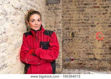 Concentrated Craftswoman Leaning Against Brick Wall In Bare Brickwork