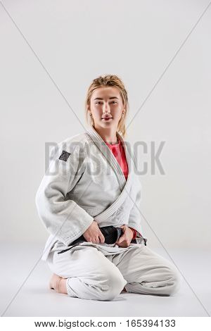 The female judokas fighter posing on gray studio