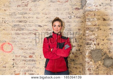 Concentrated Craftswoman In Front Of Brick Wall In Bare Brickwork