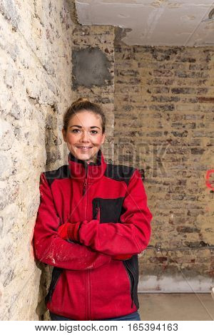 Dynamic Craftswoman Leaning Against Brick Wall In Bare Brickwork