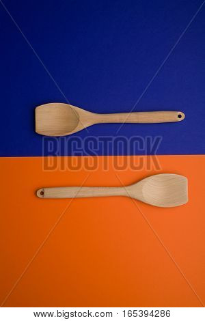 twoo Wooden Spoon over blue and orange background