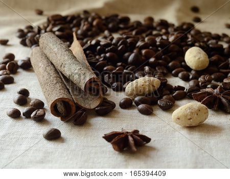 Cinnamon stickscoffee beansanise and white chocolate almond candies still life, food background