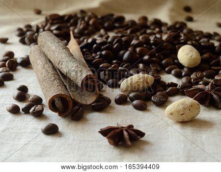 Cinnamon stickscoffee beansanise and white chocolate almond candies still life, food background