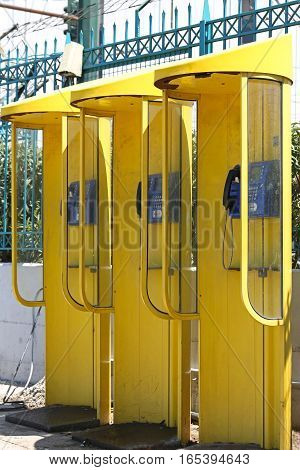 Three Yellow Pay Phone Cabins in Greece