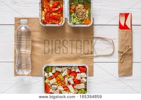 Healthy food delivery. Take away of natural organic fitness dishes for diet. Daily ratio meals in foil boxes on white wood. Craft package, vegetables, meat and salads. Top view, flat lay