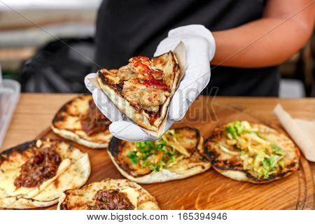 Female street vendor hands show fresh roasted meat and vegetables taco outdoors. Mexican cuisine snacks, fast food of commercial kitchen.
