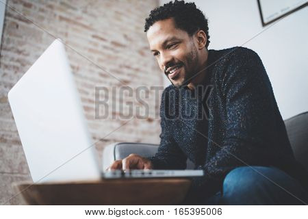 Happy african man dressed in grey pullover and typing on laptop, smiling while sitting on the sofa. Blurred background