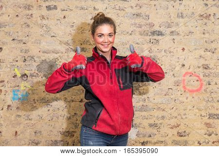 Dedicated Craftswoman With Thumbs Up In Front Of Brick Wall In Bare Brickwork