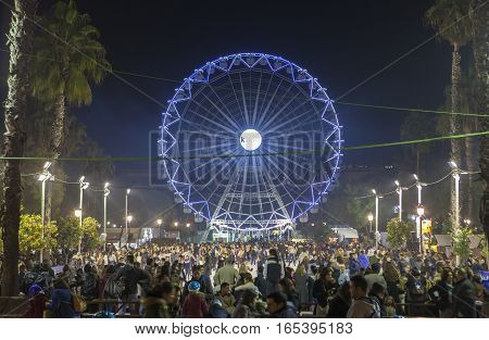 Seville Spain - January 3 2017: People enjoy visiting Christmas market with ferris wheel and ice rink
