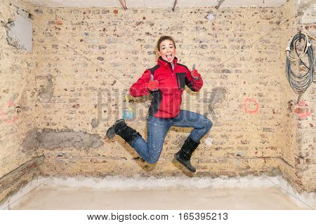 Jumping Craftswoman With Thumbs Up In Front Of Brick Wall In Bare Brickwork