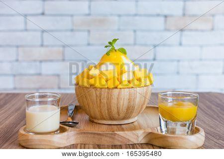 Bingsu (Korea food) mango served with sweetened condensed milk on table