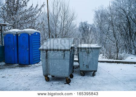 Garbage bins and toilet cubicles in the background Winter Park trees snow cold