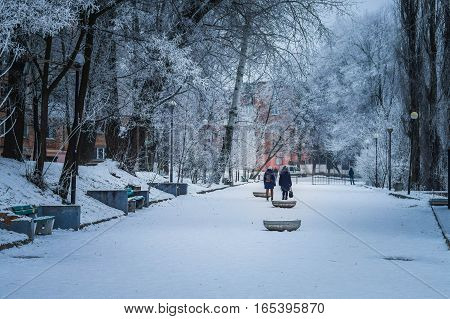 Winter street of a small town urban alley people trees frost