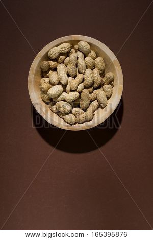 Roasted peanuts in bowl over brown background