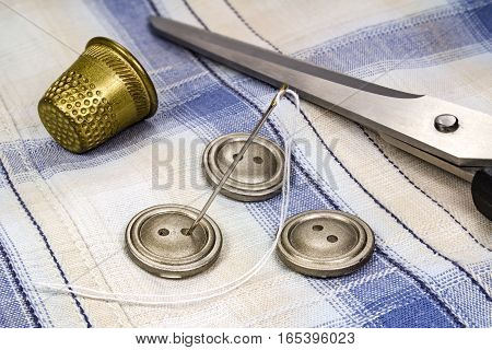Buttons needle with thread thimble and scissors on fabric background