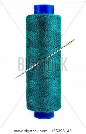 A needle and thread on a plastic spool on white background