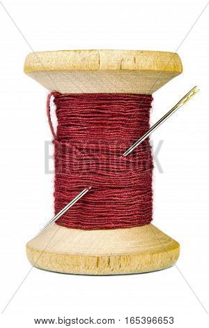Vintage wooden spool of thread and needle on white background