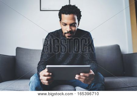 Selective focus. Attractive bearded African man using tablet while sitting on sofa in his modern home office. Concept of young business people working at home. Blurred background