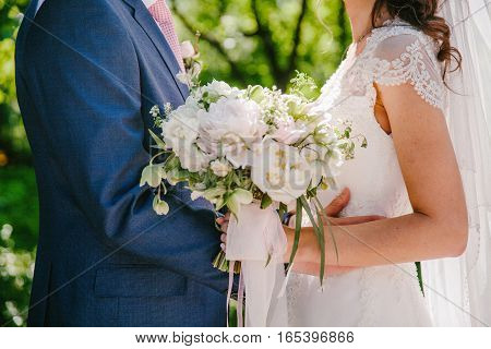 Bride and groom holding wedding bouquet together