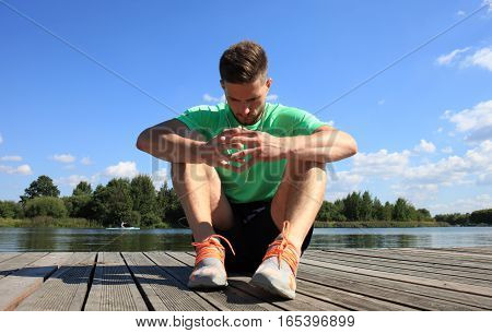 Happy tired athlete sitting in the park at sunrise
