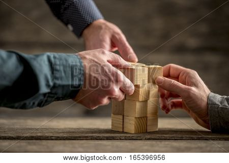 Hands of three people building a tower of wood blocks on a table teamwork concept.