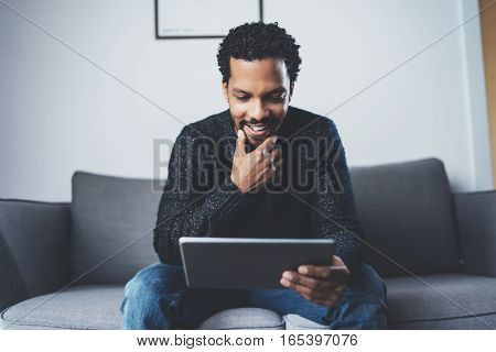 Cheerful African man using pc tablet and smiling while sitting on the sofa in his modern room.Concept of young business people working at home.Blurred background