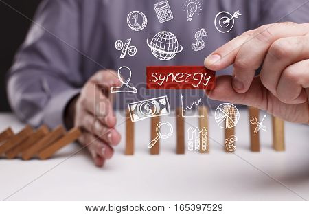 Business, Technology, Internet And Network Concept. Young Businessman Shows The Word: Synergy