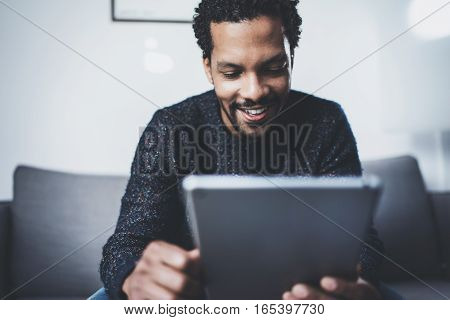 Selective focus. Closeup view of attractive young African man reading news on digital tablet while sitting sofa in his studio. Concept modern business people working home. Blurred background