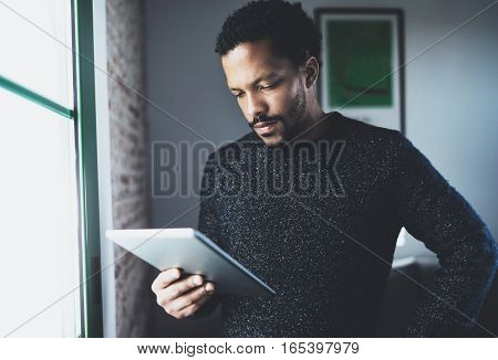 Selective focus. Pensive bearded African man using tablet while standing near the window in his modern apartment. Concept of young business people working at home. Blurred background
